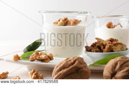 Detail Of Crystal Glasses With Creamy Yogurt With Chopped Nuts Isolated Background. Front View.
