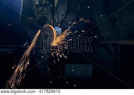 Close Up Of Fitter In Special Suit Cutting With Rotating Disc For Metal With Large Sparks. Concept O