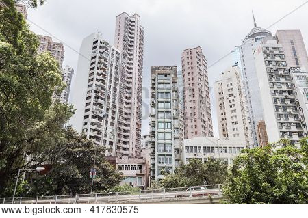 Hong Kong City Skyline, Tall Living Houses Skyscrapers Under Cloudy Sky In A Summer Day