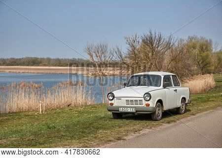 Tiszafured, Hungary - Circa 2021: Trabant, old east german comminist cheap compact car parked on the lakeside