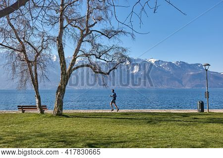 Vevey, Switzerland - Circa 2021: PArk with view over Lake Geneva, man going on a morning run in awe inspiring scenery