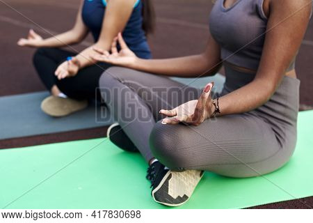 Close Frame Of Hands In Mudra Gesture Of Women Doing Yoga Outdoors. Caucasian And Black Woman Sittin