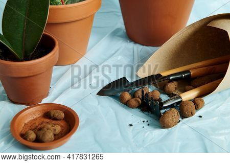 Expanded Clay In A Clay Tray With A Set Of Garden Tools Wrapped In Craft Paper Against The Backgroun