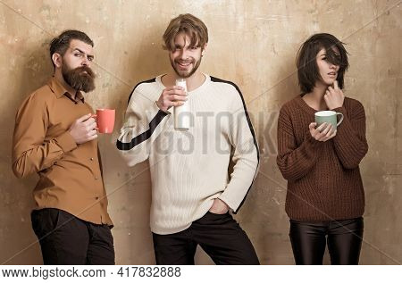 Group People Drinking Milk Or Yogurt From Cups And Smiling Man From Bottle On Beige Wall. Friendship