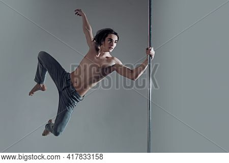 Pole Dancer. Sexy Muscular Men With Bare Naked Body Torso. Pole Dancing Guy Makes Figure On Pole.