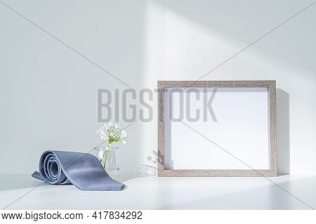 Blanc Wooden Frame Mockup. Gray Satin Tie, Small White Flowers In The Sunlight. Elegant Wedding And