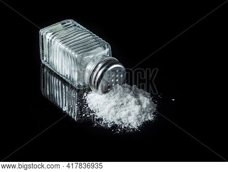 Heap Of Salt From A Salt Shaker On A Black Background. The Concept Of Excessive Salt Intake That Can