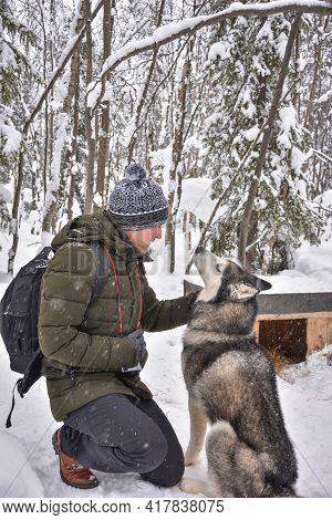 A Man Posing With A Husky On A Chain Near A Booth In A Snowy Forest
