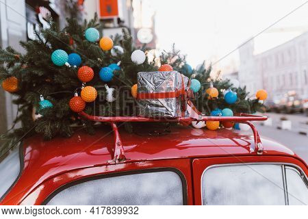 Red Retro Car With A Christmas Tree Fir Tied To The Roof.