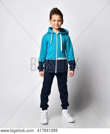 Fashion Boy Child In Warm Sportswear Suit Standing On Studio. Male Kid Advertising Sportive Outerwea