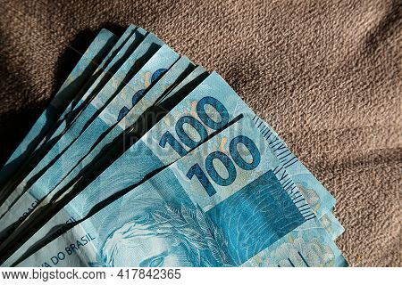 Money From Brazil Stacked On A Matte Surface And Directed Light - Several Hundred Real Bills