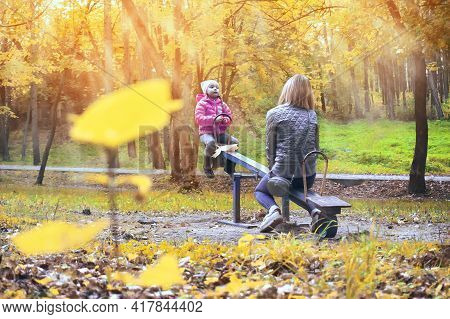 Mother And Baby Daughter Swing On A Swing In The Park. A Sunny Summer Day For Outdoor Entertainment