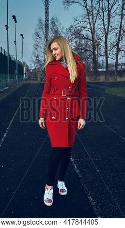 The Girl In The Red Coat Stands And Looks Away. The Girl On The Opposite Court. Stylish Red Coat. Au