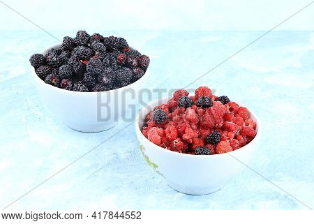 Fresh Red Raspberries And Black Raspberries, Blackberries In A Cup On A Light Background, Selective