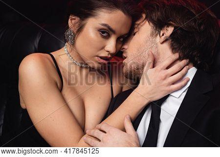 Passionate Woman In Slip Dress Seducing Man On Black.