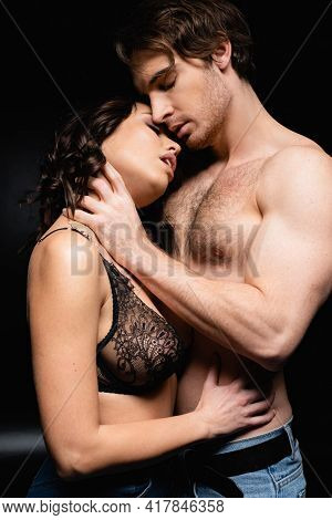 Muscular Man Hugging Seductive Brunette Woman On Black.