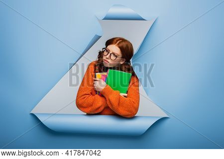Redhead Student In Orange Sweater And Glasses Holding Textbooks On Blue Ripped Paper Background.