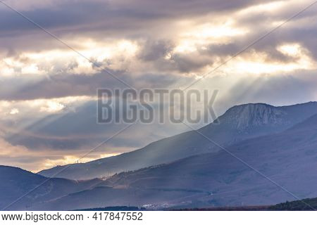 Southern Coast Of Crimea At Sunset In Winter. Sunset Rays Of The Sun Break Through The Clouds. Mount