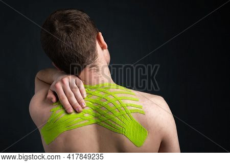 Hand Of Young Man Holding His Neck With Striped Kinesiology Medical Tape Applied To Relieve Back Pai