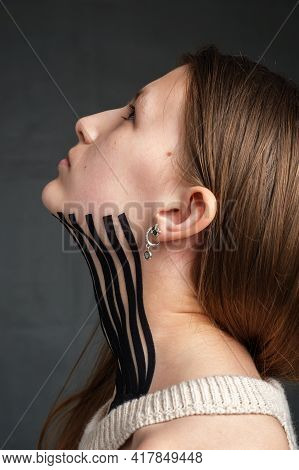 Black Striped Kinesiology Tape Placed On The Neck Of A Young Caucasian Teenager Girl On Dark Backgro