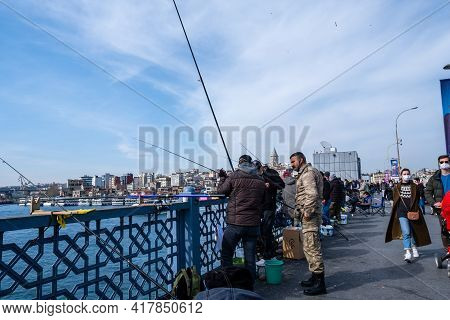 Eminonu, Istanbul, Turkey - 04.13.2021: Several Fishermen With Protective Masks Talking And Fishing