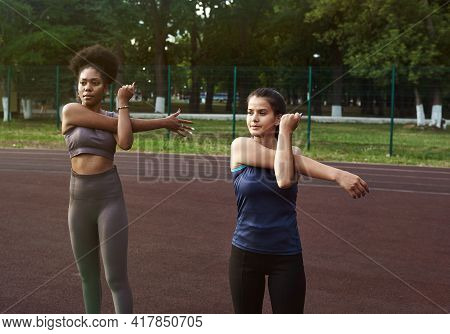 Two Women Of Different Nationalities Warm Up Before Training Outdoors. Warming Up Muscles Before Str