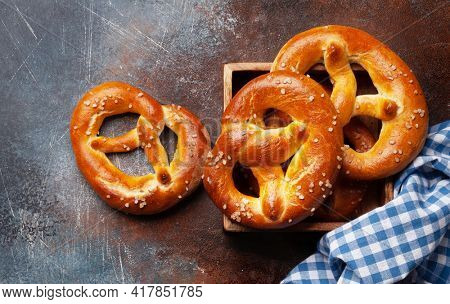 Fresh baked homemade pretzel with sea salt on stone table. Classic beer snack. Top view flat lay