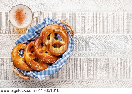 Lager beer mug and fresh baked homemade pretzel with sea salt on wooden table. Classic beer snack. Top view flat lay with copy space