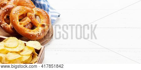 Potato chips and fresh baked homemade pretzel with sea salt on wooden table. Classic beer snack. With copy space
