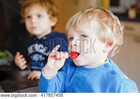 Two Little Toddler Boys, Cute Brother Children Watching Cartoons On Tv And Eating Lolipop Candy. Hap