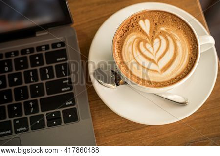 Close-up Of Hot Coffee Latte With Latte Art Milk Foam In Cup Mug And Laptop Computer On Wood Desk Of