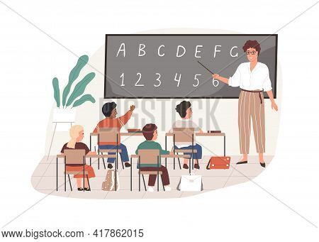 Young Teacher With Pointer At Chalkboard In Classroom. Elementary School Children Studying In Class