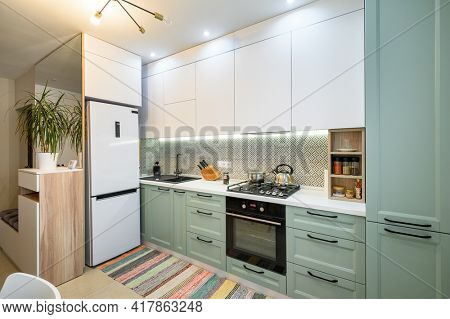 Wide shot of cozy well designed teal and white modern kitchen interior