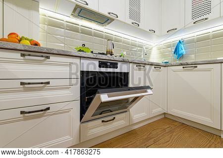 Small white cozy and comfy contemporary classic kitchen interior, electric oven door is open