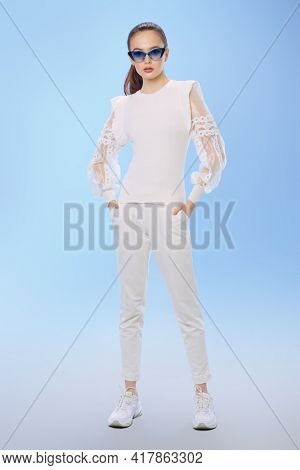 Full length portrait of a attractive girl posing in elegant white summer clothes and sunglasses on a light blue background. Summer fashion and makeup.