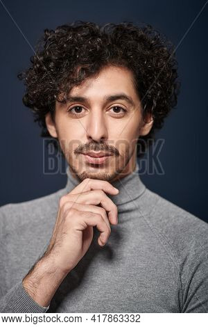 Close up portrait of a handsome young man with curly dark hair on a black background. Men's beauty.