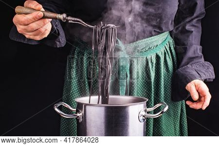 The Cook Is In The Kitchen. Hands Of Cook And Italian Black Spaghetti On The Fork. Background Of A G