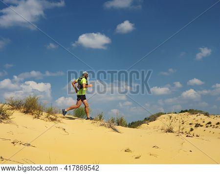 Athlete Runs Along The Sandy Desert. Desert Trail Running. A Man In Shorts And A T-shirt Is Running
