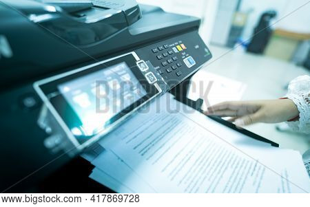 Office Worker Print Paper On Multifunction Laser Printer. Copy, Print, Scan, And Fax Machine In Offi