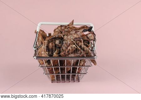 Shopping Basket With Dog Treats On A Pink Background. Natural Treats In A Metal Basket. Dried Beef L