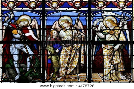 Stained glass window in St.Sulpice church (Fougeres France) depicting (from left to right) The Archangels: Michael Raphael and Gabriel. poster
