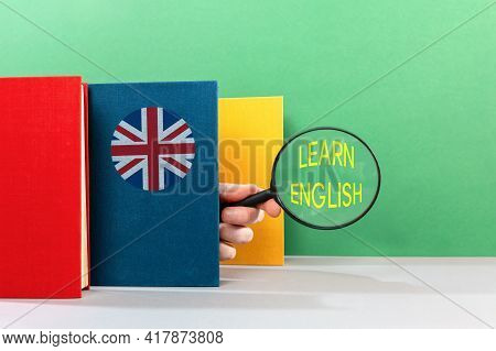 English Language Day Concept. A Male's Hand Peeks Out From Behind An English Textbook And Holds A Ma