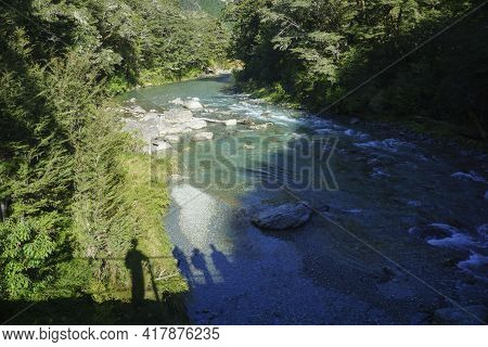 Shadows Of Travellers On Bridge Over  River Through Luxuriant New Zealand Native Forest With Deep Gr