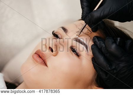 Closeup Of Beautiful Woman In Beauty Salon. Permanent Makeup. Beautician Doing Eyebrow Tattooing For