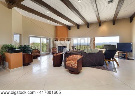Living room in luxury home with fireplace and picture windows.