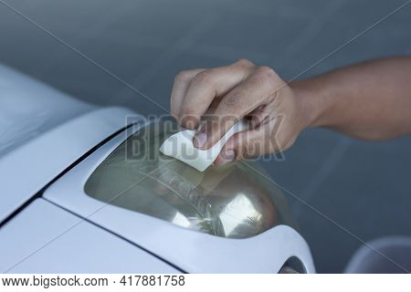 Hand Of Man Holding A Sponge To Polishing The Car Headlights That Are Yellow To Clear Up.