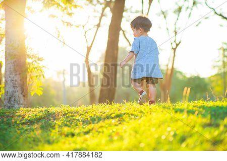 Adorable Little Asian Boy Walking On Green Grass Sunset Light In Summer Park