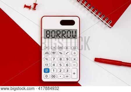 Calculator With The Word Borrow On Display With Red Notepad And Office Tools