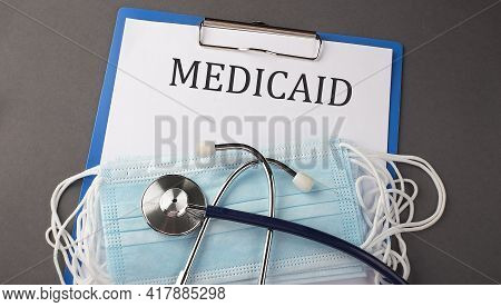 Folder With Paper Text Medicaid , On A Table With A Stethoscope And Medical Masks, Medical