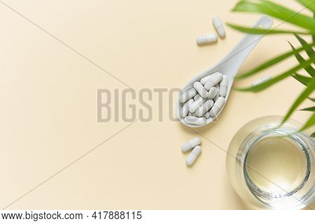 Collagen Pills In A Spoon And A Glass Of Water On A Beige Background With A Copy Space. Extra Protei